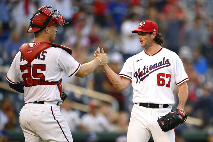 Washington Nationals relief pitcher Kyle Finnegan (67) celebrates with catcher Riley Adams (25) after a baseball game against the Toronto Blue Jays, Wednesday, Aug. 18, 2021, in Washington. The Nationals won 8-5. (AP Photo/Nick Wass)