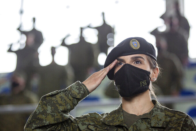 A Kosovo Security Force (KSF) member wearing a face mask salutes, during a peacekeeping mission deployment ceremony held at the army barracks in Pristina, Tuesday, March 9, 2021. Kosovo is sending a military platoon to Kuwait, its first ever involvement in an international peacekeeping mission. A ceremony was held Tuesday at the army barracks in the capital, Pristina, with the presence of top country leaders and western military attaches. Kosovo is sending the military unit following a request from the U.S. Central Command. (AP Photo/Visar Kryeziu)