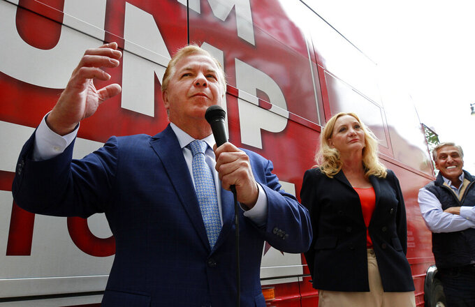 Mark McCloskey, left, and his wife Patricia, St. Louis homeowners who confronted protesters with guns, speak during a Team Trump bus tour campaign stop in Hazleton, Pa., Wednesday, Sept. 30, 2020, At right is former Hazleton Mayor Lou Barletta. (Warren Ruda/Standard-Speaker via AP)