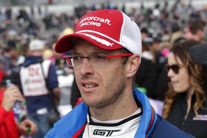 FILE - In this Jan. 26, 2019, file photo, Sebastian Bourdais, of France, walks down pit road before the IMSA 24-hour race at Daytona International Speedway, in Daytona Beach, Fla. Bourdais parted ways with Dale Coyne Racing on Friday, Nov. 22, 2019, and will move from IndyCar to sports cars in IMSA in 2020. The announcement came after several weeks of negotiations between Coyne and Bourdais, who had a year remaining on his contract but support from engine provider Honda had been pulled for the Frenchman after Bourdais failed to score any manufacturer points in 2019. (AP Photo/John Raoux, File)