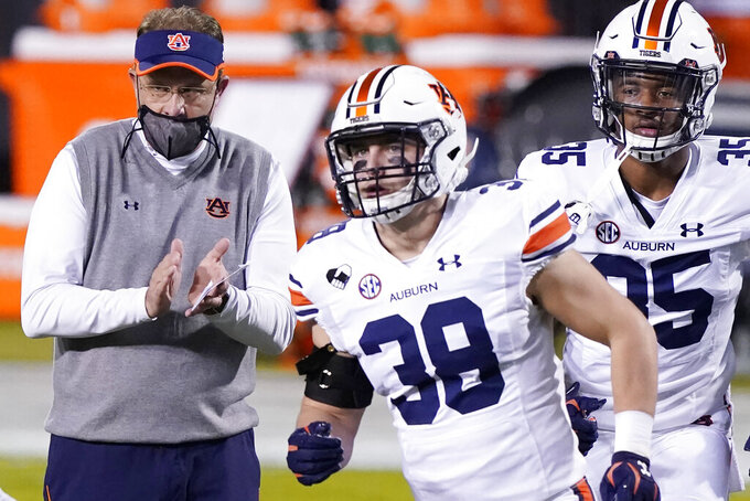 Then Auburn head coach Gus Malzahn cheers on linebacker Barrett Tindall (38) and other players during warmups prior to an NCAA college football game against Mississippi State, Saturday, Dec. 12, 2020, in Starkville, Miss. Auburn athletic director Allen Greene announced the coach's firing on Sunday, Dec. 13, 2020, a day after the Tigers finished the regular season with a 24-10 victory over Mississippi State. (AP Photo/Rogelio V. Solis)