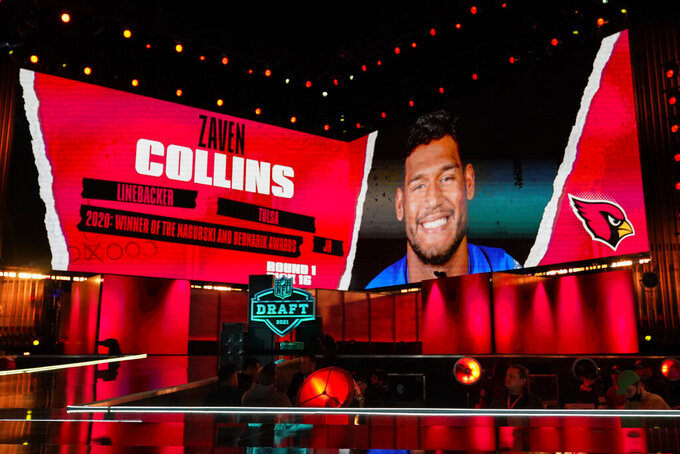 An image of Tulsa linebacker Zaven Collins is displayed on stage after he was chosen by the Arizona Cardinals with the 16 pick in the first round of the NFL football draft Thursday April 29, 2021, in Cleveland. (AP Photo/Tony Dejak)