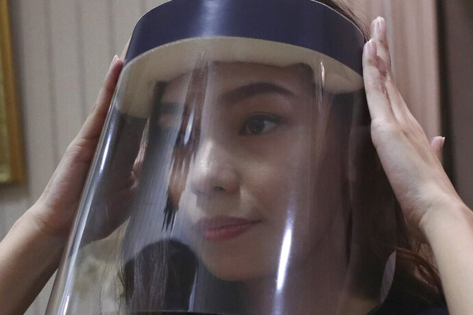 Tri Novia Septiani fixes her face shield while she attends an online memorial service for her fiance Dr. Michael Robert Marampe, to mark the 40th day since Marampe passed away due to COVID-19 in Jakarta, Indonesia, on June 5, 2020. Marampe knew what he wanted to be since he was a kid: a doctor and a pianist. He became both, and his passion for music even led him to Septiani - a woman he never got to marry because he got the coronavirus. Marampe became one of dozens of doctors the coronavirus has claimed so far in Indonesia. (AP Photo/Tatan Syuflana)