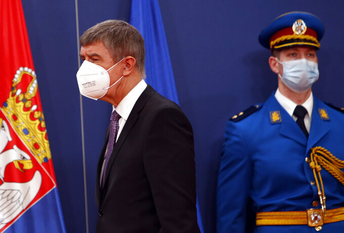 Czech Prime Minister Andrej Babis, left, arrives at a press conference after talks with his Serbian counterpart Ana Brnabic at the Serbia Palace in Belgrade, Serbia, Wednesday, Feb. 10, 2021. Babis is on a one-day official visit to Serbia. (AP Photo/Darko Vojinovic)
