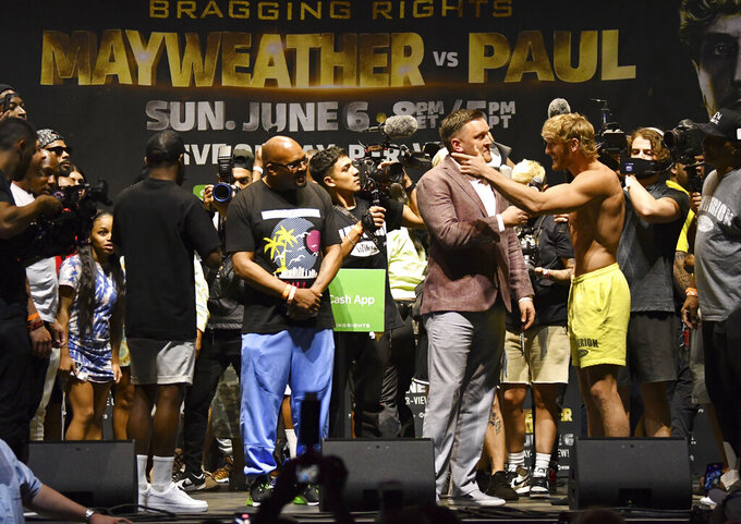 Logan Paul points at Floyd Mayweather, back to camera at eft, as they pose for photographers during a weigh-in Saturday, June 5, 2021, in Hollywood, Fla. Paul is scheduled to face Mayweather in an exhibition boxing match at Hard Rock Stadium in Miami Gardens, Fla., Sunday. (AP Photo/Jim Rassol)