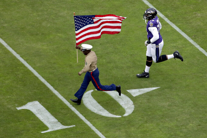 Baltimore Ravens offensive tackle Ronnie Stanley (79) runs with a U.S. service member as part of the team's Salute to Service prior to an NFL football game against the Houston Texans, Sunday, Nov. 17, 2019, in Baltimore. (AP Photo/Julio Cortez)
