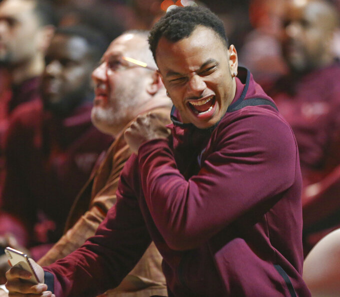 Virginia Tech's Justin Robinson, right, reacts next to coach Buzz Williams as team members watch the broadcast of the NCAA men's Division I basketball tournament selection show in Blacksburg Va., Sunday, March 17 2019. Virginia Tech was awarded a No. 4 seed and will face No. 13 seed Saint Louis in the NCAA men's Division I basketball tournament in San Jose, Calif., Friday. (Matt Gentry/The Roanoke Times via AP)