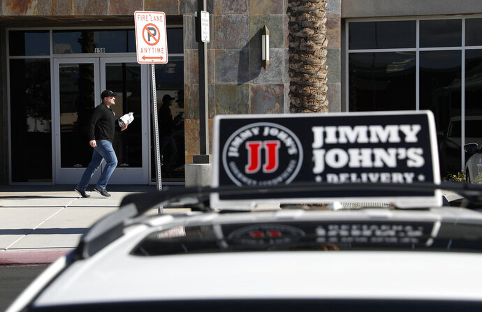 FILE - In this Feb. 6, 2019, photo, Tyler Schwecke, a delivery driver for Jimmy John's, makes a delivery in Las Vegas. Despite pressure from third-party apps, a few big chains continue to use their own drivers, and they're hiring. (AP Photo/John Locher, File)