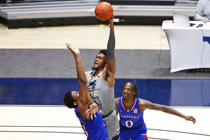 West Virginia forward Derek Culver (1) shoots while defended by Kansas forward David McCormack (33) and guard Marcus Garrett (0) during the first half of an NCAA college basketball game Saturday, Feb. 6, 2021, in Morgantown, W.Va. (AP Photo/Kathleen Batten)