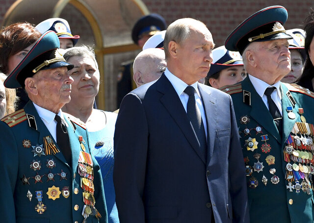 Russian President Vladimir Putin, center, stands between two WWII veterans as he takes part in a wreath laying ceremony at the Tomb of Unknown Soldier in Moscow, Russia, Monday, June 22, 2020, marking the 79th anniversary of the Nazi invasion of the Soviet Union. (Alexei Nikolsky, Sputnik, Kremlin Pool Photo via AP)