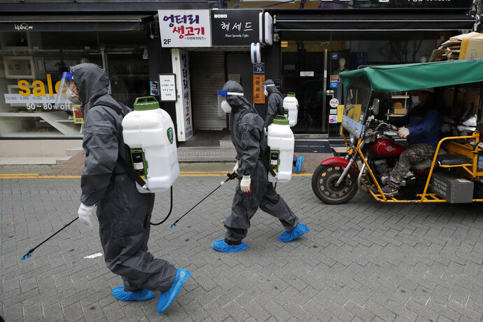 Health officials from the district office wearing protective gears disinfect as a precaution against the coronavirus as a man wearing a face mask rides a motorcycle in Incheon, South Korea, Thursday, Sept. 17, 2020. (AP Photo/Lee Jin-man)