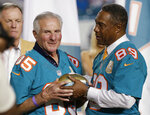 FILE - In this Dec. 14, 2015, file photo, former Miami Dolphins player Nick Buoniconti (85) is presented a football by former player and current Dolphins senior vice president of special projects and alumni relations, Nat Moore (89) during the Dolphins All-Time 50th Anniversary Team ceremony during half time at an NFL football game against the New York Giants, in Miami Gardens, Fla. Pro Football Hall of Fame middle linebacker Nick Buoniconti, an undersized overachiever who helped lead the Miami Dolphins to the NFL's only perfect season, has died at the age of 78. Bruce Bobbins, a spokesman for the Buoniconti family, said he died Tuesday, July 30, 2019, in Bridgehampton, N.Y. (AP Photo/Wilfredo Lee, File)