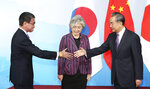Chinese Foreign Minister Wang Yi, right, shakes hands with Japanese Foreign Minister Taro Kono, left, as  South Korean counterpart Kang Kyung-wha, center, looks on, ahead of their meeting in Beijing Wednesday, Aug. 21, 2019. (Kyodo News via AP)