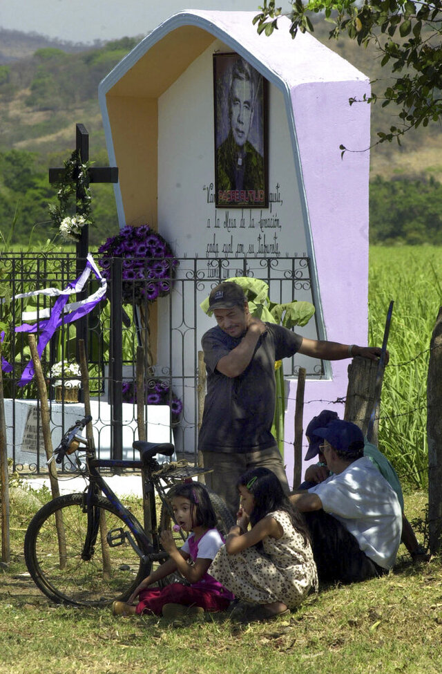 FILE - In this March 12, 2005 file photo, farmers rest in Aguilares, El Salvador, beside a monument dedicated to the Rev. Rutilio Grande, a Jesuit priest who inspired St. Oscar Romero and was himself a victim of El Salvador's right-wing death squads. Pope Francis approved a decree Friday, Feb.22, 2020, proclaiming Grande a martyr for the Catholic faith, as well as two Salvadorans who were killed along with him. (AP Photo/Edgar Romero, File)