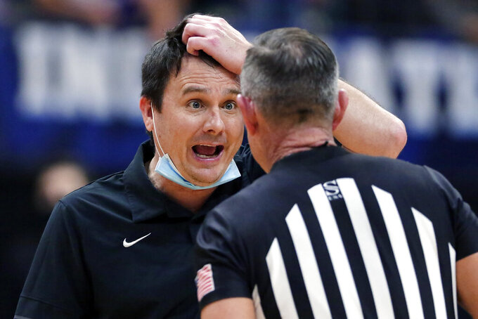 Abilene Christian coach Joe Golding argues a foul call with an official during the second half of the team's NCAA college basketball game against Nicholls State for the Southland Conference men's tournament championship Saturday, March 13, 2021, in Katy, Texas. (AP Photo/Michael Wyke)