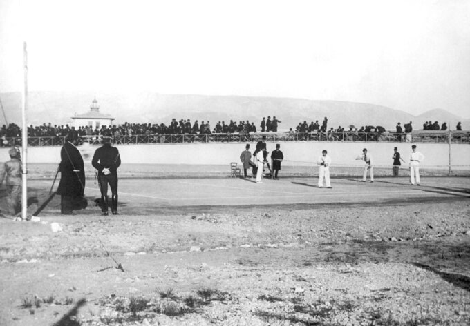 FILE - This April 11, 1896, file photo shows a doubles tennis match, Germany's Friedrich Traun and Ireland's John Pius Boland against Greek players Dionysios Kasdaglis and Demetrios Petrokokkinos, during the Summer Olympic Games in Athens, Greece.  From that modest start in Athens with 241 participants in 43 events, the Olympics have ballooned to include 11,238 athletes vying for 306 gold medals at the 2016 Games in Rio de Janeiro. More are expected for the Tokyo Olympics that were postponed one year because of the coronavirus pandemic. (AP Photo/File)