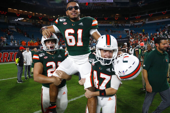 Miami's Bubba Baxa (21) and Turner Davidson (47) carry out Jacob Munoz (61) as they celebrate after Miami defeated Louisville 52-27 during an NCAA college football game Saturday, Nov. 9, 2019, in Miami Gardens, Fla. (AP Photo/Wilfredo Lee)