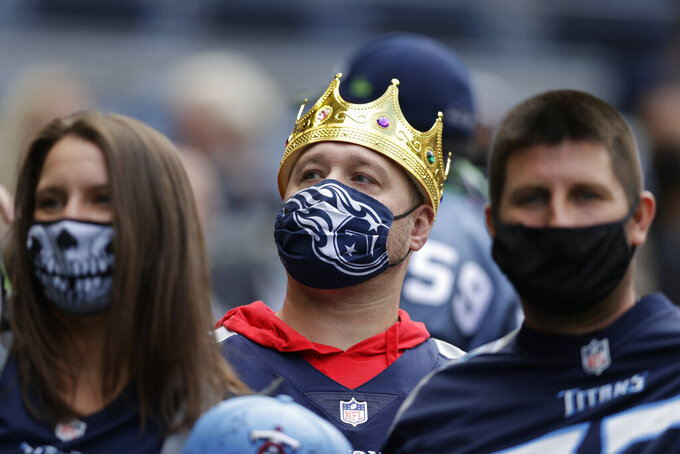 Tennessee Titans fans wear masks due to the COVID-19 pandemic before an NFL football game between the Seattle Seahawks and the Tennessee Titans, Sunday, Sept. 19, 2021, in Seattle. (AP Photo/John Froschauer)