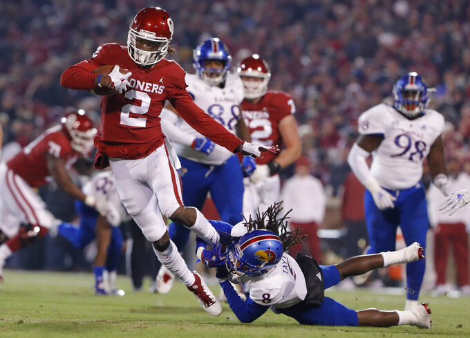 Oklahoma wide receiver CeeDee Lamb (2) is tackled by Kansas cornerback Shakial Taylor (8) during the first half of an NCAA college football game in Norman, Okla., Saturday, Nov. 17, 2018. (AP Photo/Alonzo Adams)