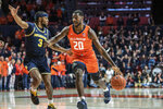 Illinois' Da'Monte Williams (20) moves the ball as Michigan's Zavier Simpson (3) defends in the first half of an NCAA college basketball game, Wednesday, Dec. 11, 2019, in Champaign, Ill. (AP Photo/Holly Hart)