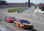 Martin Truex Jr. (19) and Daniel Suarez (41) head through Turn 1 during the NASCAR Cup Series auto race at Auto Club Speedway in Fontana, Calif., Sunday, March 17, 2019. (AP Photo/Rachel Luna)