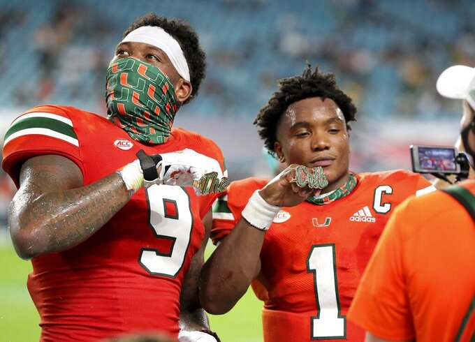 Miami tight end Brevin Jordan (9) and quarterback D'Eriq King (1) display their touchdown rings in the third quarter during an NCAA college football game against UAB in Miami Gardens, Fla., Thursday, Sept. 10, 2020. (Al Diaz/Miami Herald via AP)