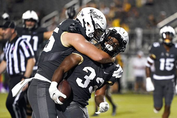 Central Florida running back Trillion Coles (33) celebrates his touchdown against Bethune-Cookman with tight end Zach Marsh-Wojan, left, during the second half of an NCAA college football game, Saturday, Sept. 11, 2021, in Orlando, Fla. (AP Photo/John Raoux)
