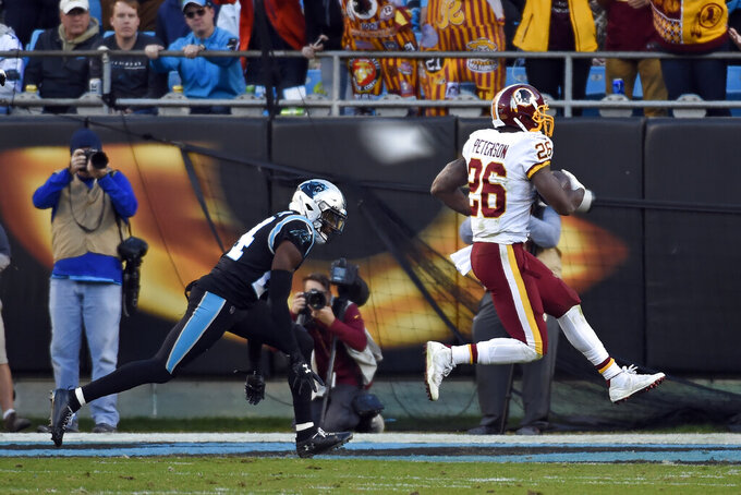 Washington Redskins running back Adrian Peterson (26) scores a touchdown while Carolina Panthers cornerback James Bradberry chases during the second half of an NFL football game in Charlotte, N.C., Sunday, Dec. 1, 2019. (AP Photo/Mike McCarn)