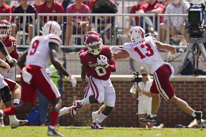 Oklahoma running back Eric Gray (0) carries past Nebraska defenders Marquel Dismuke (9) and JoJo Domann (13) in the second half of an NCAA college football game, Saturday, Sept. 18, 2021, in Norman, Okla. (AP Photo/Sue Ogrocki)