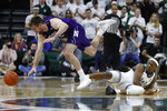 Northwestern guard Pat Spencer, left, chases the loose ball and trips over Michigan State guard Cassius Winston (5) during the first half of an NCAA college basketball game, Wednesday, Jan. 29, 2020, in East Lansing, Mich. (AP Photo/Carlos Osorio)