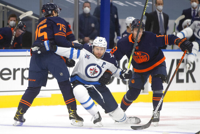 Edmonton Oilers' Evan Bouchard (75) and Kyle Turris (8) defend against Winnipeg Jets' Blake Wheeler (26) during the third period of an NHL hockey game Wednesday, Feb. 17, 2021, in Edmonton, Alberta. (Jason Franson/The Canadian Press via AP)