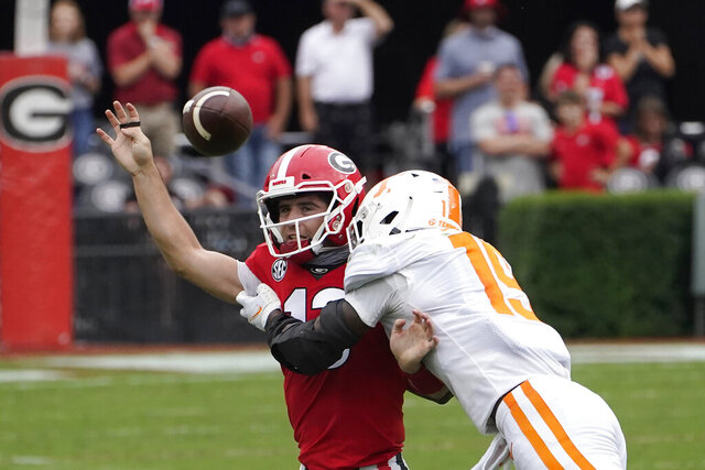 Georgia quarterback Stetson Bennett (13) is hit by Tennessee linebacker Morven Joseph (19) as he releases a pass in the first half of an NCAA college football game Saturday, Oct. 10, 2020, in Athens, Ga. (AP Photo/John Bazemore)