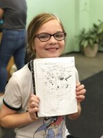 In this June 8th, 2018 photo provided by Syed Ali Haider, 10-year-old Genevieve Thiel shows off her work during Austin Bat Cave's week-long Magical Realism summer camp in Austin, Texas. Educators say teaching critical and creative writing is just as important as strong reading and is too often overlooked.