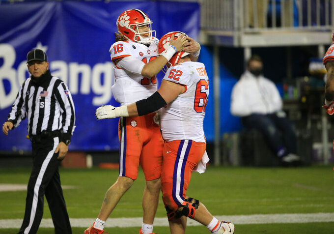 Clemson quarterback Trevor Lawrence (16) celebrates his touchdown with offensive lineman Cade Stewart (62) during the second half of the Atlantic Coast Conference championship NCAA college football game against Notre Dame, Saturday, Dec. 19, 2020, in Charlotte, N.C. (AP Photo/Brian Blanco)