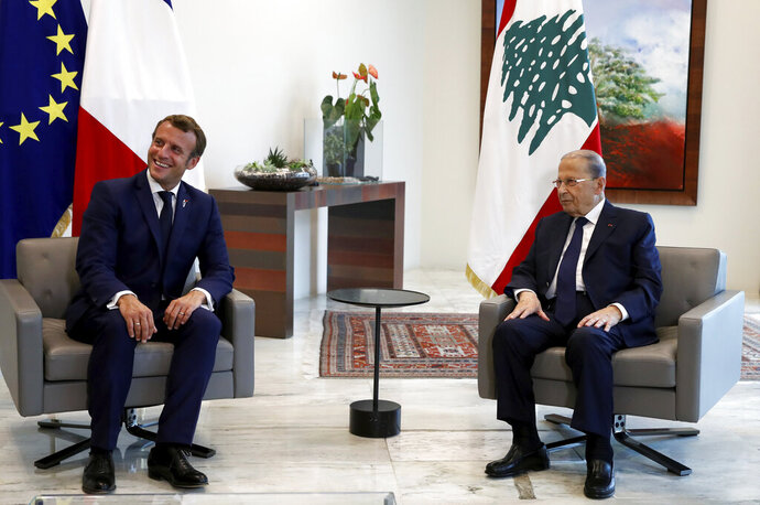 """FILE - In this Sept. 1, 2020 file photo, French President Emmanuel Macron, left, smiles as he meets Lebanon's President Michel Aoun at the presidential palace in Baabda, Lebanon, Tuesday, Sept. 1, 2020. In a televised address Monday, Sept. 21, 2020, Aoun warned that the crisis-hit country could be going to """"hell"""" if a new government is not formed. An initiative led by Macron called for a Lebanese government of independent specialists that was to be formed by Sept. 15. (Gonzalo Fuentes/Pool via AP, File)"""