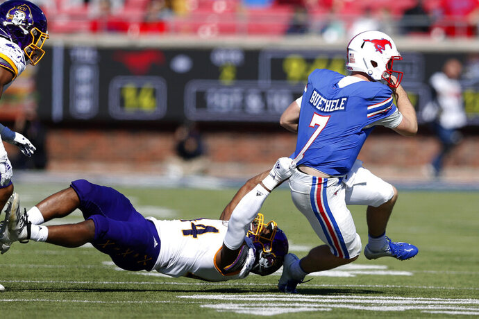 SMU quarterback Shane Buechele (7) fights for yards as East Carolina defensive end Kendall Futrell, left, tackles him during the first half of an NCAA college football game, Saturday, Nov. 9, 2019, in Dallas. SMU beat East Carolina 59-51. (AP Photo/Roger Steinman)