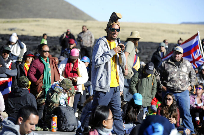 Kaho'okahi Kanuha, wearing a traditional Hawaiian battle helmet, addresses a group of protesters who are continuing their opposition vigil against the construction of the Thirty Meter Telescope at Mauna Kea on the Big Island of Hawaii Friday, July 19, 2019. Hundreds of protesters trying to stop the construction of a giant telescope on land some consider sacred continue to gather at the base of Hawaii's tallest mountain on Friday, July 19, 2019, as Democratic presidential candidate Bernie Sanders expressed his support for the demonstration. (Bruce Asato/Honolulu Star-Advertiser via AP)
