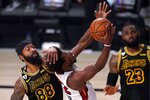 Los Angeles Lakers' Markieff Morris (88) delivers a hand to the head of Miami Heat's Jimmy Butler on a shot attempt as LeBron James (23) looks on during the first half of Game 2 of basketball's NBA Finals, Friday, Oct. 2, 2020, in Lake Buena Vista, Fla. (AP Photo/Mark J. Terrill)