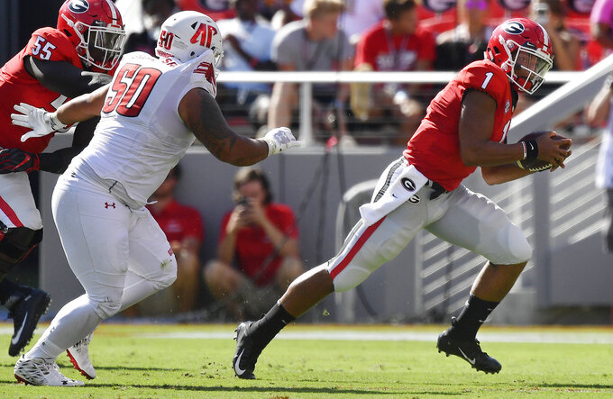 Georgia quarterback Justin Fields (1) runs out of the pocket as Austin Peay defensive lineman Corey Brown (50) chases during the first half of an NCAA college football game, Saturday, Sept. 1, 2018, in Athens, Ga. (AP Photo/Mike Stewart)