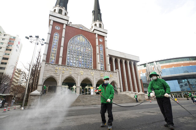 Workers wearing face masks spray disinfectant as a precaution against the new coronavirus in front of Myungsung Church in Seoul, South Korea, Wednesday, Feb. 26, 2020. The number of new virus infections in South Korea jumped again Wednesday and the U.S. military reported its first case among its soldiers based in the Asian country, with his case and many others connected to a southeastern city with an illness cluster. (Yun Dong-jin/Yonhap via AP)