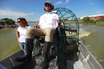 Wildlife biologist/crocodile specialist Michael Lloret, center, pilots an airboat as Bianca Soriano, left, Florida Power and Light (FPL) spokesperson, rides along, through a section of the cooling canals next to the Turkey Point Nuclear Generating Station, Friday, July 19, 2019, in Homestead, Fla. The 168-miles of man-made canals serve as the home to several hundred crocodiles, where a team of specialists working for FPL monitors and protects the American crocodiles. (AP Photo/Wilfredo Lee)