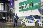 """FILE - In this Saturday, Sept. 4, 2021, file photo, an armed police officer stands outside a Countdown supermarket in Auckland, New Zealand. Ahamed Aathil Samsudeen grabbed a kitchen knife from store shelf and begins stabbing shoppers while chanting """"Allahu akbar"""" — meaning """"God is great"""" at the supermarket on Sept. 3, 2021. (AP Photo/Brett Phibbs, File)"""
