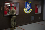 In this June 17, 2020, photo made available by the U.S. Air Force, a member of security forces stands at the 316th Security Support Squadron armory window to receive weapons and equipment for his shift at Joint Base Andrews, Md. Using government records covering the Army, Marines, Navy and Air Force, an Associated Press investigation showed that military pistols, machine guns, shotguns and assault rifles vanished from armories, supply warehouses, Navy warships, firing ranges and other places where they were used, stored or transported. (Senior Airman Kaylea Berry/U.S. Air Force via AP)