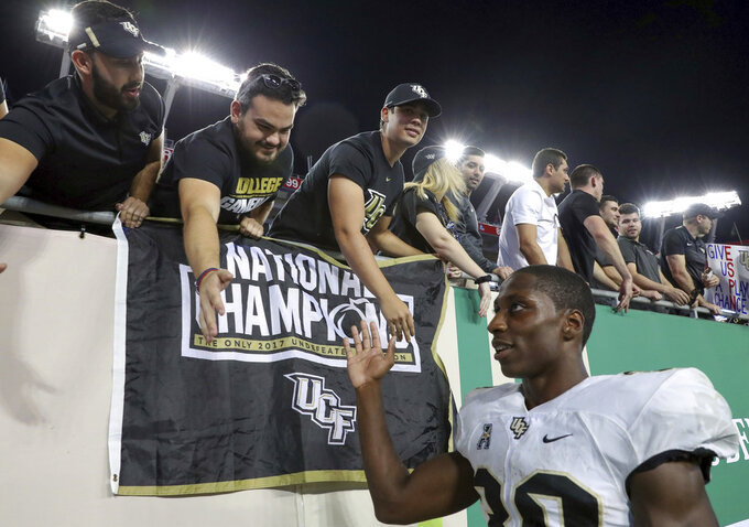 Central Florida's Greg McCrae, right, celebrates with fans after a win over South Florida in an NCAA college football game Friday, Nov. 23, 2018, in Tampa, Fla. (AP Photo/Mike Carlson)