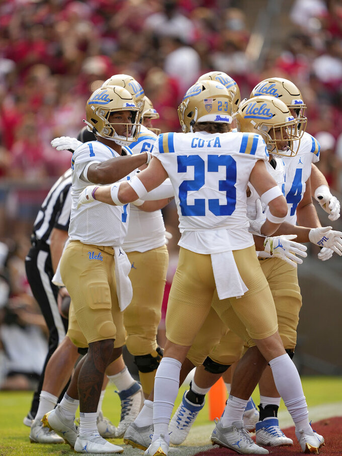UCLA quarterback Dorian Thompson-Robinson (1) celebrates with wide receiver Chase Cota (23) after scoring a touchdown against the Stanford during the first half of an NCAA college football game Saturday, Sept. 25, 2021, in San Francisco, Calif. (AP Photo/Tony Avelar)