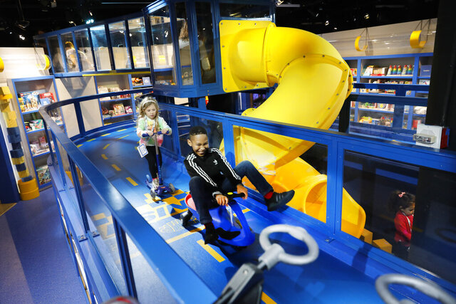 In this Nov. 21, 2019 photo, children ride scooters on an elevated loop, at Camp toy store in New York. Camp, which was founded last year, not only sells toys but has also workshops and interactive areas for children. The concept is expanding to other locations and is the latest offering in experiential retail. (AP Photo/Mark Lennihan)