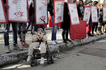 FILE - In this Jan. 13, 2018 file photo, family members of Tunisians who died in the revolution seven years ago, stage a protest in Tunis, while a child in a baby-stroller rests in front of them. Since winning a parliamentary seat in 2019, Tunisian lawmaker Abir Moussi has become one of the country's most popular, and most controversial, politicians, riding a wave of nostalgia for a more stable and prosperous time, just as Tunisia marks 10 years since protesters overthrew autocratic former President Zine El Abidine Ben Ali. Since 2011, Tunisia has been plagued by sinking wages, growing joblessness and worsening public services. Unemployment has risen amid the coronavirus pandemic from 15% to 18%. Attempts to migrate to Europe by sea have soared. (AP Photo/Hassene Dridi, File)