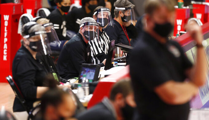 Officials on the scorer's table watch wear face masks and shields during the second half of an NCAA college basketball game between North Florida and NC State at Reynolds Coliseum in Raleigh, N.C., Wednesday, Nov. 25, 2020. (Ethan Hyman/The News & Observer via AP)