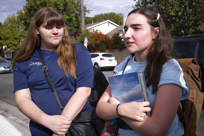 Saugus high students Georgia McDow, left, and Audrey Marshall, both 17, talk about going back on campus at Saugus high Tuesday, Nov. 19, 2019. Students were allowed back to collect their belongings left behind after the tragic shooting last Thursday. Classes will resume at the high school on Dec. 2. (David Crane/The Orange County Register via AP)