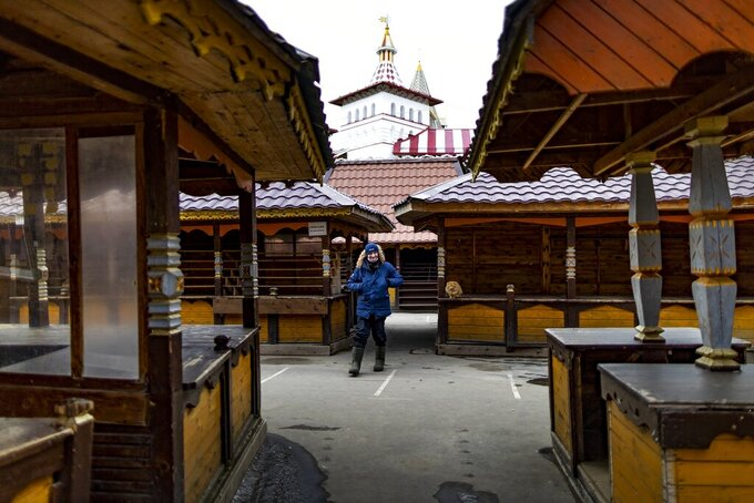 """A security worker walks through an empty market near a boutique hotel called Skazka – or """"Fairytale"""" -- in eastern Moscow on Tuesday, March 23, 2021. One year later, Skazka is still open — thanks to some creative thinking by its owners — but with many fewer guests than before the pandemic. (AP Photo/Alexander Zemlianichenko)"""